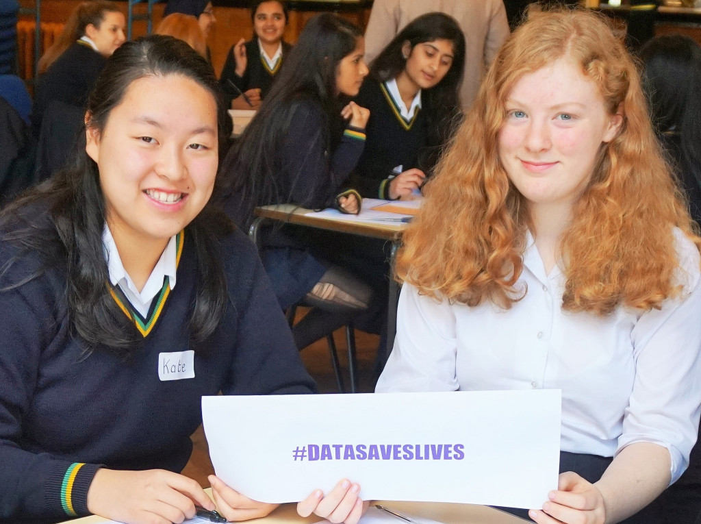 Two pupils hold a #datasaveslives sign in support of the campaign