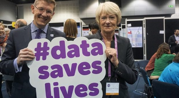 Prof. Iain Buchan and Dame Nancy Rothwell holding #DataSavesLives sign