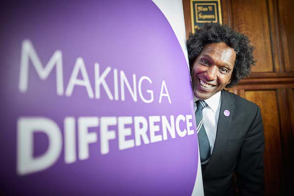 Lemn Sissay next to Making a Difference banner at the University of Manchester